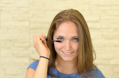 Jolie jeune femme appliquant l'eye-liner Photographie stock