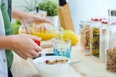 Jolie jeune femme appréciant le petit déjeuner dans la cuisine Images libres de droits