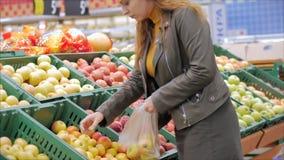 Jolie jeune femme aux cheveux rouges achète de la nourriture, des fruits, des pommes sur le marché, dans le supermarché. La fil banque de vidéos