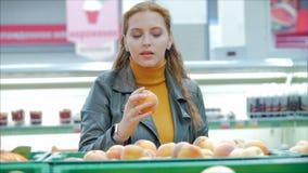 Jolie jeune femme aux cheveux rouges achète de la nourriture, des fruits, des pommes sur le marché, dans le supermarché. La fil clips vidéos
