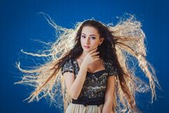Jolie jeune femme avec de longs cheveux sur le fond bleu Images stock