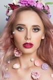 Jolie jeune femme avec la guirlande des fleurs roses Images stock