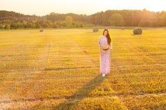 Jolie jeune femme avec le chapeau se tenant en foin dans le domaine de chaume Image libre de droits
