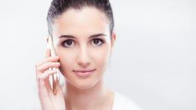 Jolie jeune femme ayant un appel téléphonique photographie stock libre de droits