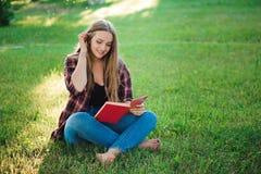 Jolie jeune femme blonde lisant un livre au parc image libre de droits