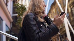 Jolie jeune femme caucasienne dans la veste et les lunettes de soleil marchant avec un smartphone dans ses mains et écouteurs de  clips vidéos