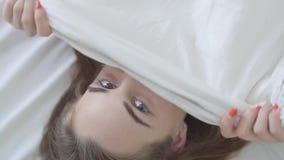 Jolie jeune femme caucasienne heureuse de portrait avec différents yeux colorés se situant dans le lit le matin couvrant son visa banque de vidéos