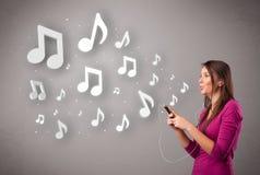 Jolie jeune femme chantant et écoutant la musique avec n musical photos libres de droits