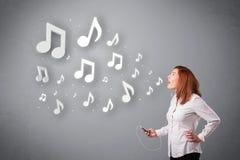 Jolie jeune femme chantant et écoutant la musique avec n musical Image stock
