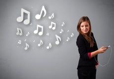 Jolie jeune femme chantant et écoutant la musique avec n musical Image libre de droits