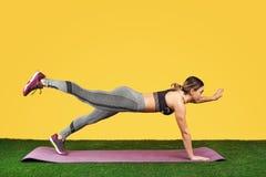 Jolie jeune femme convenable faire l'exercice sur le tapis pourpre de forme physique sur l'herbe verte au-dessus du fond jaune photographie stock libre de droits