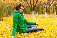 Jolie jeune femme détendant en parc d'automne Photo stock