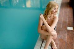 Jolie jeune femme détendant par la piscine photographie stock