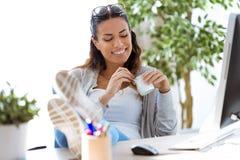Jolie jeune femme d'affaires mangeant du yaourt tout en faisant une pause dans le bureau image libre de droits