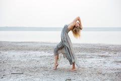 Jolie jeune femme dans la robe dansant nu-pieds sur la plage Photographie stock libre de droits