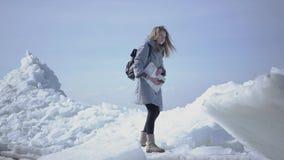 Jolie jeune femme dans la veste chaude marchant sur le glacier, tenant son téléphone portable dans la main augmentée, essayant de clips vidéos