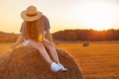 Jolie jeune femme dans le chapeau se reposant sur une balle de foin Photo libre de droits