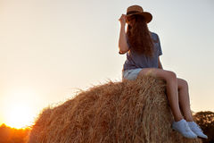 Jolie jeune femme dans le chapeau se reposant sur une balle de foin Image libre de droits