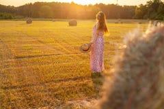 Jolie jeune femme dans le chapeau tenant la balle de foin proche Images stock