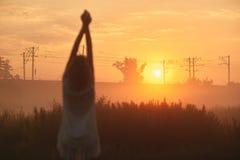 Jolie jeune femme dans le domaine au coucher du soleil Images stock