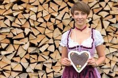 Jolie jeune femme dans un dirndl tenant un coeur Photographie stock libre de droits