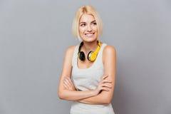 Jolie jeune femme de sourire à l'aide des écouteurs se tenant avec des bras croisés Photographie stock libre de droits