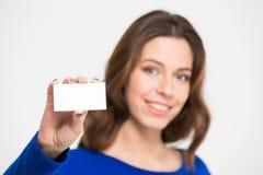 Jolie jeune femme de sourire tenant et montrant la carte vierge Images stock