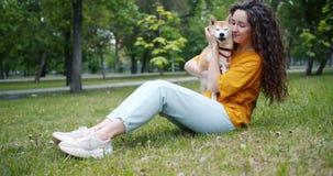 Jolie jeune femme embrassant le museau et la séance de sourire du chien sur l'herbe en parc clips vidéos