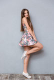 Jolie jeune femme espiègle posant sur une jambe Photo stock