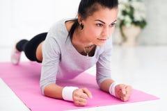 Jolie jeune femme faisant l'exercice abdominal de planche Image libre de droits