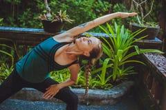 Jolie jeune femme faisant le yoga dehors dans l'environnement naturel Images stock