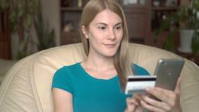 Jolie jeune femme futée s'asseyant dans la chaise à la maison Achat en ligne avec la carte de crédit sur le smartphone clips vidéos