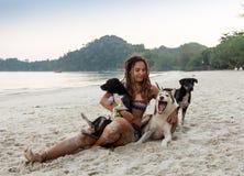 Jolie jeune femme gaie dans le chapeau reposant et étreignant son chien sur la plage Photos stock