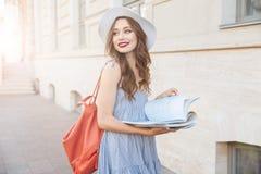 Jolie jeune femme heureuse lisant un livre sur la rue photographie stock