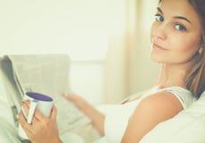 Jolie jeune femme lisant le journal dans le lit et appréciant une tasse de thé images stock