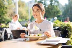Jolie jeune femme mangeant sur la terrasse de restaurant Photographie stock libre de droits