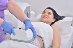 Jolie jeune femme obtenant le traitement de cryolipolyse dans le professiona Photographie stock libre de droits