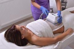 Jolie jeune femme obtenant le traitement de cryolipolyse dans le professiona Photo stock