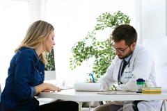 Jolie jeune femme parlant avec le jeune docteur beau au sujet de sa santé dans la consultation photos stock