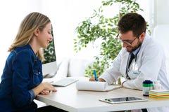 Jolie jeune femme parlant avec le jeune docteur beau au sujet de sa santé dans la consultation images libres de droits