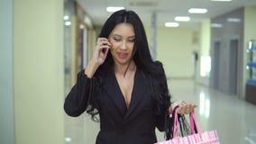 Jolie jeune femme portant beaucoup de paniers et marchant dans le mail banque de vidéos