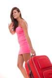 Jolie jeune femme portant la valise rouge et le sourire de voyage image libre de droits
