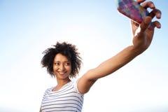 Jolie jeune femme prenant le selfie avec le téléphone portable dehors photos stock