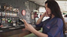 Jolie jeune femme regardant le menu dans le restaurant et corrigeant ses cheveux Fille seule se reposant dans un café clips vidéos