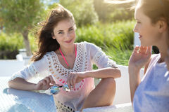 Jolie jeune femme s'asseyant avec l'ami à la table de café dehors Image stock