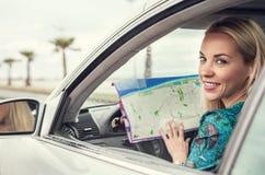 Jolie jeune femme s'asseyant dans la voiture avec une carte de routes Photos libres de droits