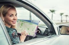 Jolie jeune femme s'asseyant dans la voiture avec une carte de routes Photos stock