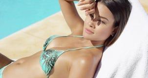 Jolie jeune femme se bronzant dans le soleil d'été banque de vidéos
