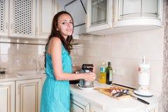Jolie jeune femme se tenant faisante cuire dans sa cuisine images libres de droits