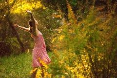Jolie jeune femme sous la pluie d'été pendant un coucher du soleil Photographie stock